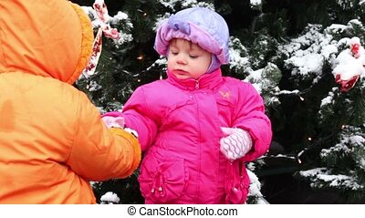 Little girl came and gives snow to another kid in pink down-padded coat