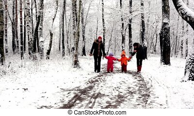 Two girls with their kids walk closer in woods where all...