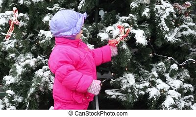 Little girl shake bow ribbon on Christmas tree covered with...