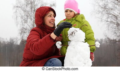 mother with daughter, turn head in small snowman - mother...