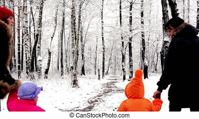 Two girls with their kids walk in woods where all covered...