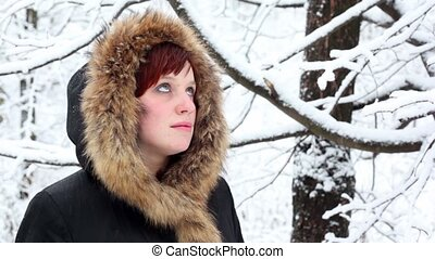 Girl in fur hood looks at falling snow
