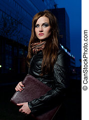 Young businesswoman in big city center at night