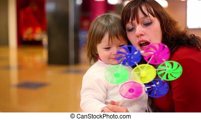 Daughter sit on mothers knees, they blow in fan toy