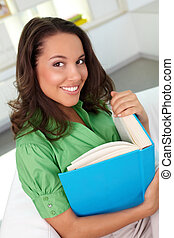 Female with book - Smiling woman looking at cam with a smile...