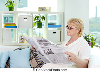 At leisure - Portrait of aged woman reading newspaper at...