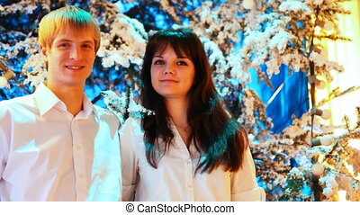 young couple stands in winter forest