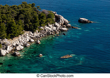 Rocks in the ocean - Beautiful blue waters which contains...