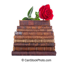 stack of antique books and red rose