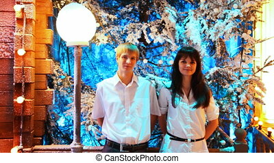 couple stands at wooden house decorated with lamps on background of forest