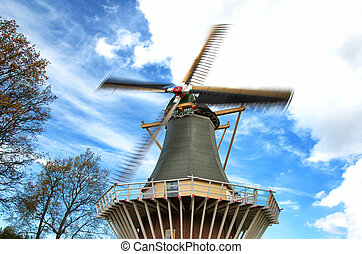 Old wind mill - Old style wind mill with blue sky as...