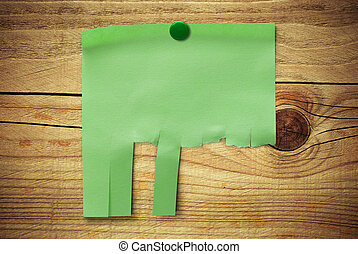 blank green note with tearable strips over wooden...