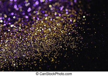 Gold and purple glitter on black background with selective...