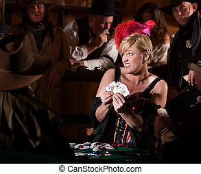 Woman Playing Cards in Saloon - Embarrassed bar maid with...