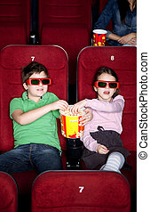 Children sharing popcorn in the 3D movie theater