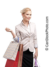 Business woman in a light beige suit holding shopping bags