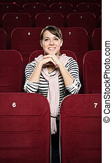 Smiling woman waiting a movie