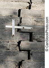 Rulers measuring the cracks in the brick wall