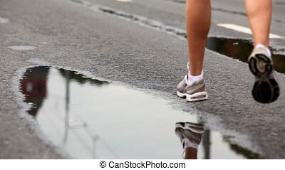 Man legs in trainers run on wet asphalt, they are reflected...