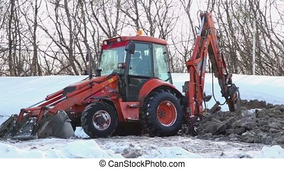 Bulldozer boring terrestrial rocks in winter, pile of ground...