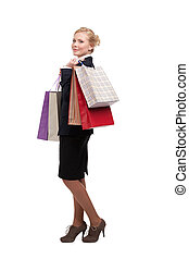 Young business woman in a black suit holding shopping bags, full length portrait