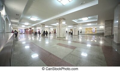 People in hall with marble floors and columns, cornerview