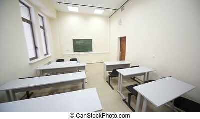 Empty beige classroom with wooden school desks and simple black chairs, view from inside