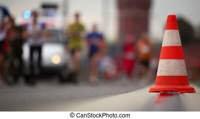 People run in sport wear and jogging shoes near orange cone on asphalt