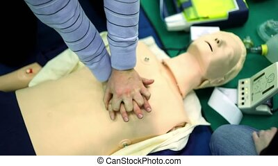 Person trains to do chest compressions on mannequin