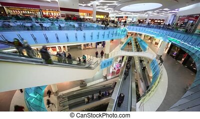 Many peoples move on escalators in multiple floors shopping...