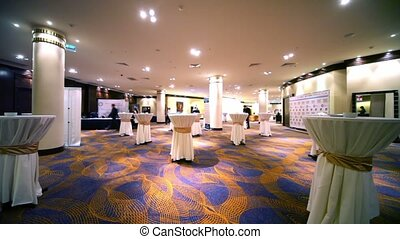 Spacious hall with columns and carpet, tables covered with...