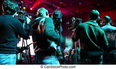 Four cameramen on workplace in row of cameras, view from...