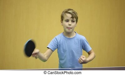 Little boy wearing blue shirt playing ping pong, he make few...