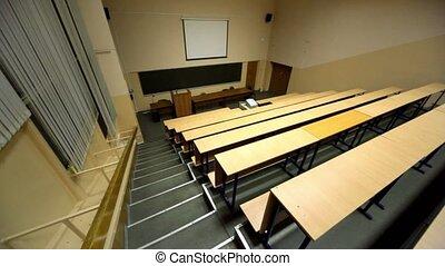 Empty lecture auditorium, white screen above blackboard,...