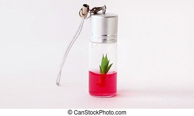 Herb in small bottle with red gel rotates slowly - Green...