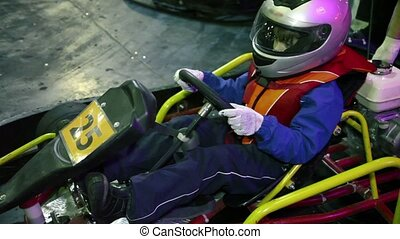 Little boy in helmet and racer suit sits in cart, coach crank an engine