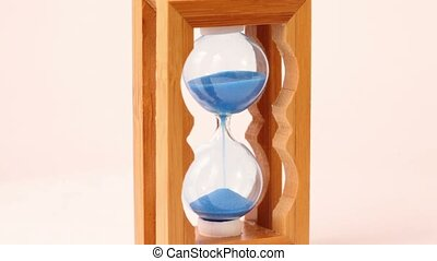 sand pours inside hourglass, which rotates and measure time