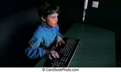 Young boy plays video game on big screen with keyboard and...