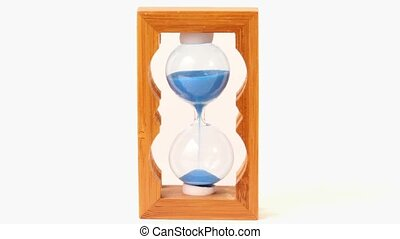 sand pours inside hourglass measured time - Blue sand pours...