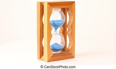 Hand take wooden framed hourglass, turn over and put it back