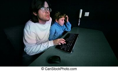 Father sit with his son in dark room and play video game on...