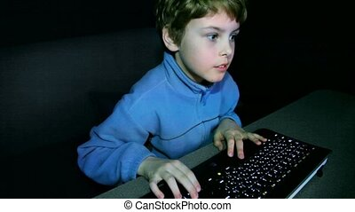 Little boy plays video game on big screen with keyboard and...