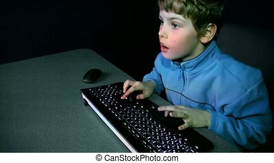 Young boy chews gum and plays video game with keyboard,...