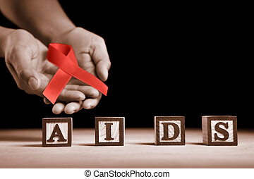 AIDS cause - Hand holding red ribbon on back of AIDS letter...