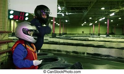 Adult instructor and little boy looking at carting ride,...