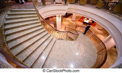 Man stand on marble circular stairs and speak cellphone