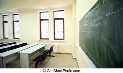 Empty beige classroom with wooden school desks and simple black chairs, view from board