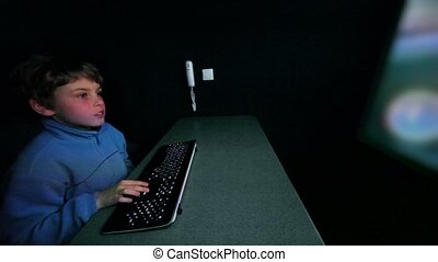 boy chews gum and plays video game with keyboard on big...