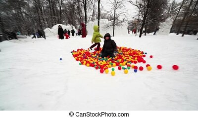Boy and little girl play in pile of colored balls in park at...