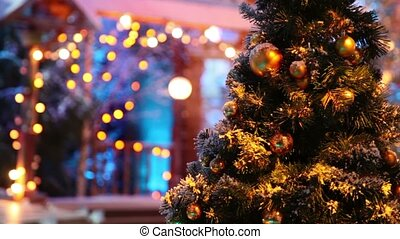 Christmas tree with balls stand in front of blurred house -...